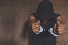 The Concept Caught, Criminal And Crime.killer With Handcuffs In The Dark. Arrested By The Police, Drug Traffickers Concept.