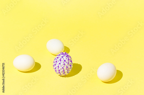 Easter spring layout with egg with purple stickers among eggs on a yellow background. Minimal spring holiday composition.