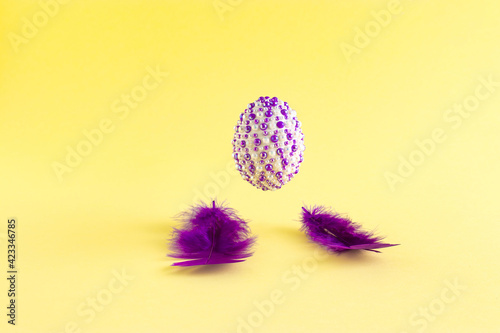 The creative Easter concept made of purple fins and natural eggs with purple stickers levitates above on a yellow background. Minimal holiday or spring concept.
