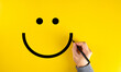 Male hand drawing a smiling happy face sketch on yellow background. Client satisfaction.