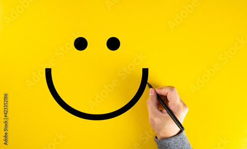 Obraz Male hand drawing a smiling happy face sketch on yellow background. Client satisfaction. - fototapety do salonu