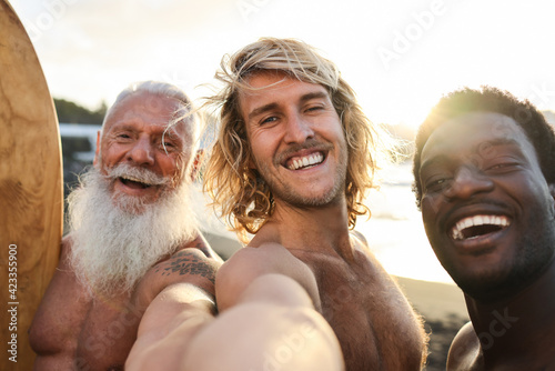 Fototapeta Multi generational surfer friends having fun on the beach after surf session - Multiracial friendship and extreme sport lifestyle concept - Main focus on center guy face obraz