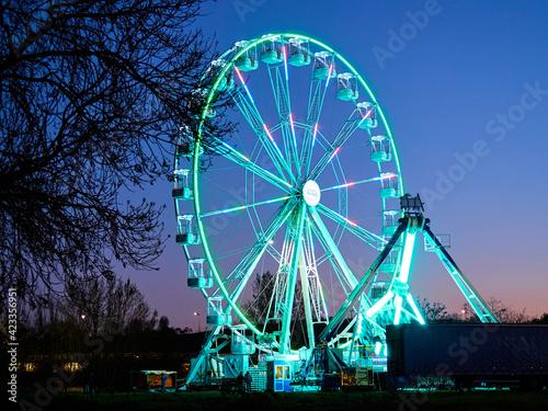 Foto Ferris wheel and amusement park at dusk, at night.