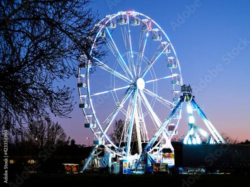 Ferris wheel and amusement park at dusk, at night. Fotobehang