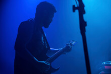 Musician Playing Electric Guitar During Rock Band Live Concert. Black Hair Male Guitar Player Performing On Stage. Music Foggy Lights Show Silhouette
