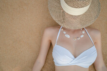 Woman In White Bikini Lying On Sand Beach Making Necklace From Sea Shell, Straw Hat Covering Her Face.