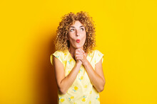 Surprised Shocked Curly Young Woman With Clasped Hands Under The Chin On A Yellow Background