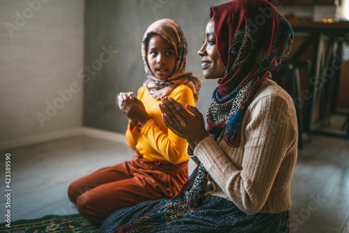 Fototapeta Muslim family praying together. Religious activity concept