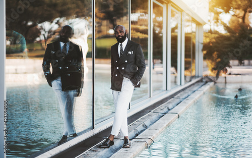 Photo A stately mature bearded bald black guy in an elegant costume with white trouser