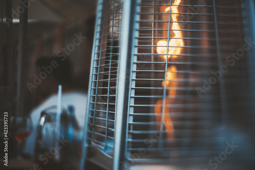 Obraz A true tilt-shift photo of a street gas heater for a patio with a flame of fire inside, with a selective focus on the part of a protective metal grid - fototapety do salonu