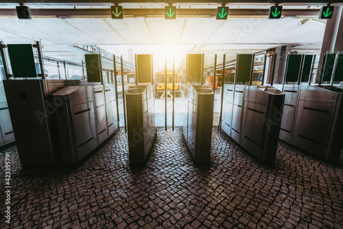 Tablou Canvas The row of turnstiles on the paving-stone with closed glass doors and green arro