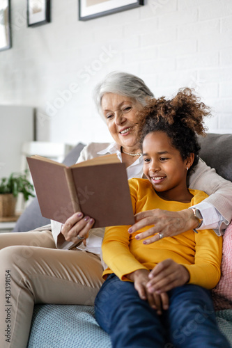 Grandmother studying with multiethnic grandchildren for school