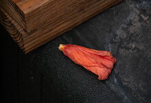 The Orange Hibiscus Bloom Is Spent For The Day And Has Dropped Off The Plant Landing On A Dark Colored Table Making A Nice Contrast Next To A Wooden Board Stand. Bokeh Effect.