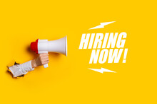 Female Hand Sticking Out Of A Hole In The Wall Holds A Megaphone On A Yellow Background. Added Text Hiring Now. Hiring Concept, Help Wanted. Banner