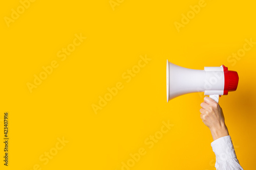 Stampa su Tela female hand holds a white with a red megaphone on a yellow background