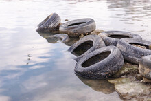 Old Tires On The Beach. Pollution Of The Reservoir With Old Car Tires. Garbage On The Shore