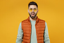 Young Shocked Amazed Surprised Scared Impressed Man 20s In Orange Vest Mint Sweatshirt Glasses Looking Camera With Opened Mouth Isolated On Yellow Color Background Studio Portrait. Lifestyle Concept.