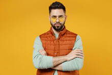 Young Serious Confident Shrewd Caucasian Man 20s In Orange Vest Mint Sweatshirt Glasses Look Camera Hold Hands Crossed Folded Isolated On Yellow Background Studio Portrait. People Lifestyle Concept