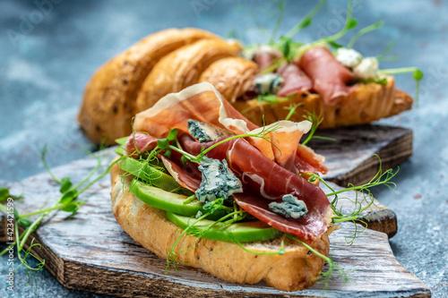 Fotografie, Obraz Croissant sandwich with jamon ham serrano paleta iberica, blue cheese, avocado, microgin on blue background
