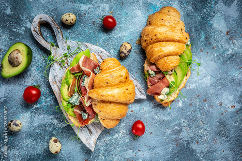 Fotografiet Variety of aperitifs Croissant sandwiches with jamon ham serrano paleta iberica, blue cheese, avocado, microgin on blue background