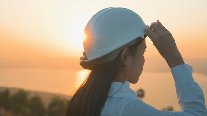 a woman engineer is putting a protective helmet on her head at sunset...