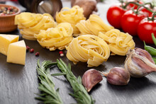 Raw Pasta Tagliatelle With Fresh Tomatoes, Peppers, Mushrooms,asparagus Beans, Spices And Cheese On Black Table.