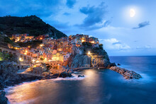 View Of Manarola Village And Moon At Night, Cinque Terre. Italy, Europe  Bright Pink Sunset At Seaport In Brindisi, Adriatic Sea. Italy