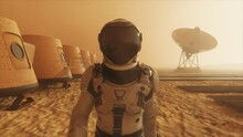 Astronaut On The Planet Mars, Making A Detour Around His Base. Astronaut Walking Along The Base. Small Dust Storm. The Satellite Dish Sends Data To The Ground. Realistic 3D Animation