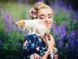 A small kitten is playing on the shoulder of a young beautiful girl in the summer nature