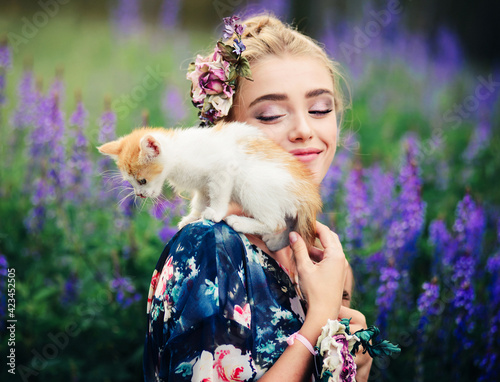 Fototapeta A small kitten is playing on the shoulder of a young beautiful girl in the summer nature obraz