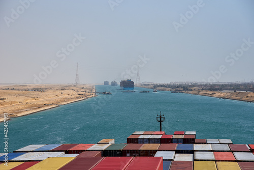 View on the containers loaded on deck of cargo ship. Vessel is transiting Suez Canal on her international trade route. Suez canal landscape.