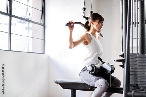 Fototapeta トレーニングジムでバックラットプルダウンをするアジア人女性 obraz