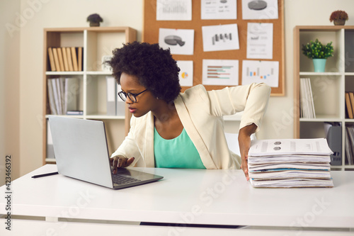 Fototapeta Convenient electronic bookkeeping vs stacks of papers. Secretary or financial accountant organizing digital documents on computer. Young woman sitting at office desk and doing paperwork on laptop obraz