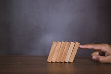 Close-up Fingers Prevent The Wooden Block From Falling Domino Concepts Of Financial Risk Management And Strategic Planning.
