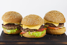 Group Of Burgers On A Wooden Board On A Light Background