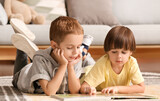 Cute little boys reading book at home