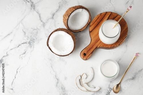 Jars of tasty coconut yogurt on light background