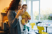 Woman Carrying Her Son And Having Coffee