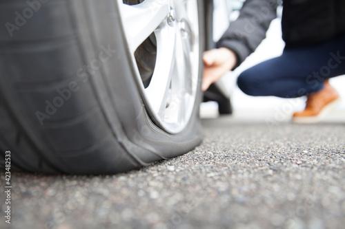 パンクしたタイヤをさわるドライバー Fotobehang