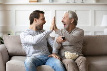 Happy Older Caucasian Father And Adult Grownup Son Give High Five Celebrate Win Watching TV Together. Overjoyed Millennial Man Have Fun Enjoy At Home With Senior Dad With Football Game.