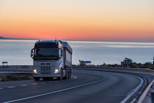 Dump Truck On A Mountain Road By The Sea With A Sunrise Background.