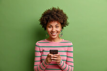 Beautiful Young African American Woman Smiles Positively Sends Text Messages Via Smartphone Enjoys Online Communication Being Always In Touch Wears Striped Jumper Isolated Over Green Background