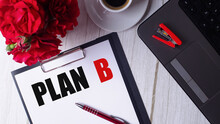 The Word PLAN B Is Written In Red On A White Notepad Near A Laptop, Coffee, Red Roses And A Pen.
