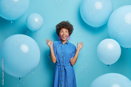 Indoor shot of positive curly haired Afro American woman raises palms dressed in festive dress looks above isolated over blue background with inflated balloons around enjoys birthday celebration