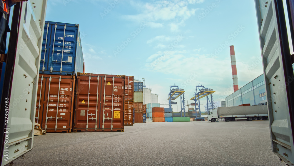 Fototapeta Low Angle Shot of an Industrial Terminal Location in a Shipyard Logistics Operations Center with Red and Blue Steel Shipping Cargo Containers Taken inside the Container. Daylight Cloudy Outdoors.