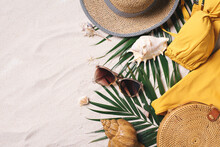Female Beach Accessories: Swimsuit, Bikini, Rattan Bag, Straw Hat, Shells, Sunglasses, Palm Leaves On Sand Background. Exotic, Tropical Mood. Summer Vacation, Travel Concept. Flat Lay. Copy Space