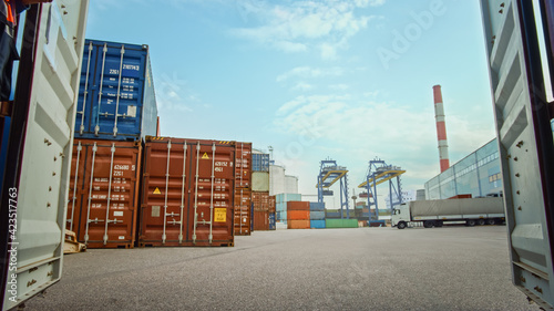 Low Angle Shot of an Industrial Terminal Location in a Shipyard Logistics Operations Center with Red and Blue Steel Shipping Cargo Containers Taken inside the Container. Daylight Cloudy Outdoors.