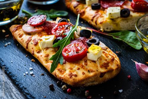 Fototapeta Focaccia - roasted mozzarella sandwiches with salami pepperoni, feta cheese and