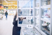 Young Woman Shopping Meat And Other Frozen Products At The Grocery Store.