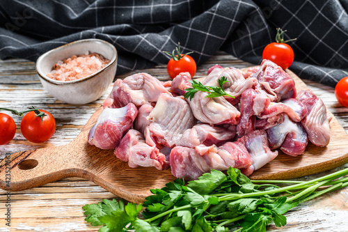 Fotografie, Obraz Raw uncooked chicken gizzards, stomach on a cutting board